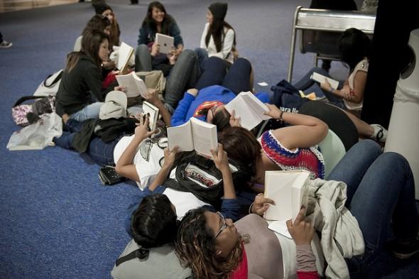 Un grupo de jóvenes lee en los pasillos de la feria.